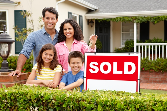 latino-family-in-front-of-home-with-sold-sign